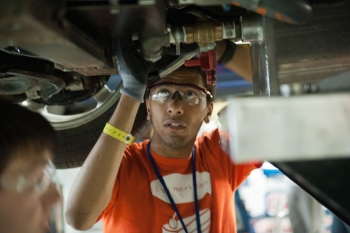 A North Carolina State University student works on an EcoCAR vehicle at the Year 3 finals last year in Milford, MI. | Energy Department photo.