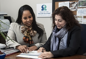 Sabrina Elam (left) and Lorri Wright, who work in procurement for SRNS, review the savings the company achieved.