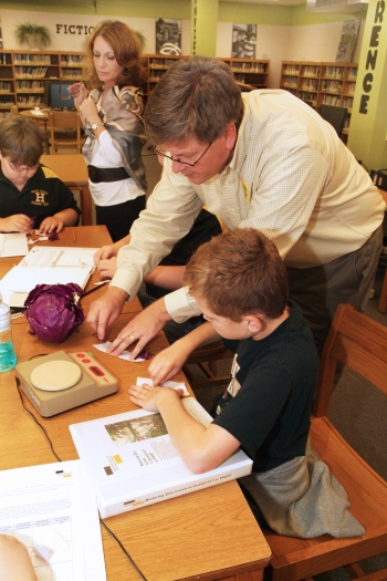 Mentor Jim Erickson of the LATA Kentucky team shows Heath Middle School sixthgrader Ian Morgan how to use red cabbage to indicate if a watery solution is acidic, basic, or neutral.