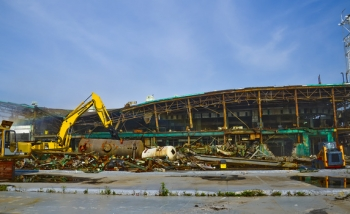 A shear-equipped excavator cuts beams to allow the roof to safely collapse.
