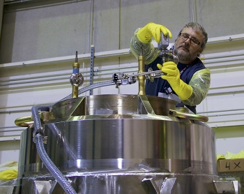 A worker prepares the cask containing 19 TRIGA fuel elements for shipment to the University of Maryland.