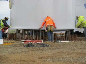 Workers line up bolts as a wind tower section is lowered at the Eva Creek Wind Farm site. The project supported 180 jobs during the construction phase. | Photo courtesy of Golden Valley Electric Association