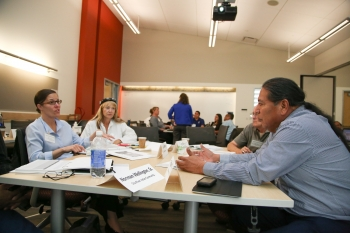 Workshop guest speaker Jana Ganion of Blue Lake Rancheria (shown here to the left sitting at a table with workshop participants) provided an inspiring story of how effective strategic energy planning can help a Tribe take a leadership role in renewable energy development. Photo by John De La Rosa, NREL