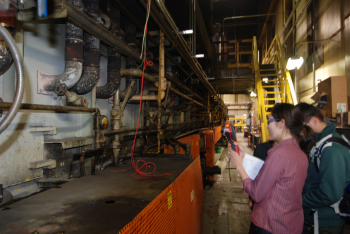 Sandina Ponte, a member of the University of Missouri's Industrial Assessment Center, inspects equipment at a manufacturing facility during an energy audit. | Photo courtesy of University of Missouri IAC.