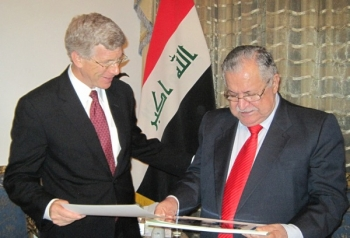 Deputy Secretary Daniel Poneman and Iraqi President Jalal Talabani exchanging official photographs as they conclude their meeting.   Energy Department Photo