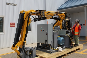 AMWTP employee Shirley Perez checks out features of new robotic arms to be installed this fall to help with legacy waste cleanup.