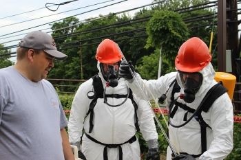 Trainer Randall Rickman, left to right, observes Larry Berg from EM's Safety, Security and Quality Programs office and Tony Pierpoint from DOE's Office of Independent Enterprise Assessments practice chemical sampling during Hazardous Waste Operations and Emergency Response initial training in Germantown, Md.