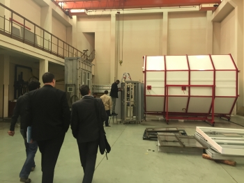"""Industry and Energy Department representatives walk towards a """"hotbox,"""" a device for systematically testing the efficiency of building materials, such as windows and doors. 