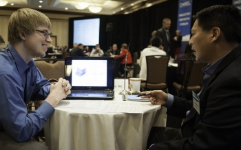"""Douglas Hitching (left), CEO of Silicon Solar Solutions and Henry Chung, LG, talk during a one-on-one networking session at the National Renewable Energy Laboratory's Industry Growth Forum in 2012. The SunShot Initiative and the National Renewable Energy Laboratory are hosting a hackathon at the SunShot Grand Challenge Summit as part of an overall effort to lower """"soft costs"""" of solar energy.   Photo by Dennis Schroeder, National Renewable Energy Laboratory"""