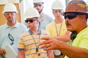 LATA Kentucky groundwater cleanup site superintendent Donnie Bell, far right, describes the project to (from left) Steve Christmas of LATA Kentucky and interns Weston Loyd, Matthew Jehnke, and Wesley Morgan.