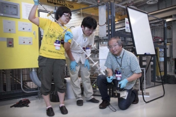 Maiko Kofu, Atsushi Nagoe and Osamu Yamamuro examine their sample attached to the end of the cryostat stick after running an experiment at Oak Ridge National Laboratory's Spallation Neutron Source. | Department of Energy Photo | Courtesy of Oak Ridge National Laboratory | Public Domain |