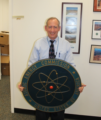 Office of Environmental Management Deputy Assistant Secretary Ken Picha holds an Atomic Energy Commission sign he found in the Forrestal Building. | Photo courtesy of Ken Picha