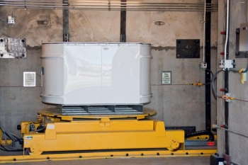 A standard waste box enters the HE-RTR at Los Alamos National Laboratory. The facility x-rays waste drums that contain high-density items such as motors and pumps and larger containers known as standard waste boxes.