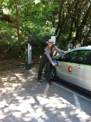"""A park ranger charges an electric vehicle at Golden Gate National Recreation Area in California.  Golden Gate is partnering with San Francisco Clean Cities for a series of projects for the <a href=""""http://www1.eere.energy.gov/cleancities/national_parks.html"""">Clean Cities National Parks Initiative</a>. Nine new projects have been announced as part of the initiative.   Photo courtesy of National Parks Service"""