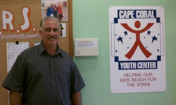 Cape Coral Youth Center Manager Mark Cagel stands in front of a tamper-proof thermostat at the Austen Youth Center in Cape Coral, Florida. | Photo Courtesy of the Cape Coral Youth Center