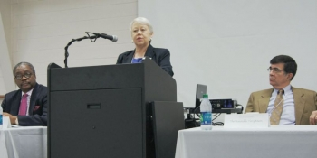 Dr. Kathy Matlock speaks at the Community Leaders' Institute in Bolton, North Carolina, while Dr. David Rivers (left) and Mayor Terry Mann (right) listen.