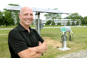 Michael Dunn, Deputy Director of Facilities Management at Argonne National Laboratory, setup a program that encouraged employees to cut their energy use during peak summer months and resulted in more than $475,000 in savings. Here he stands next to an electrical vehicle fueling station that charges cars with solar energy.   Image courtesy of Argonne National Laboratory.