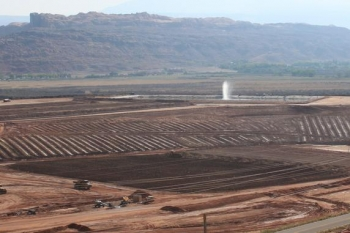 Pictured here is the Moab uranium mill tailings pile. Tailings excavation and conditioning activities are seen in the foreground. The water spray is used to eliminate extracted contaminated groundwater.