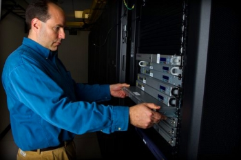 National Renewable Energy Laboratory (NREL) Technician Mic Stremel works with a blade server in the green data center at the Research Support Facility. | Image courtesy of NREL, Dennis Schroeder.