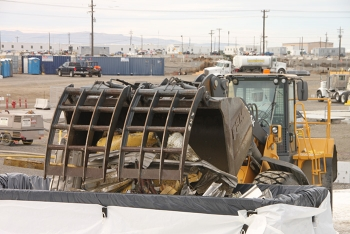 A front-end loader places demolition debris into a waste container for disposal at Hanford's regulated landfill.