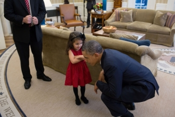 President Barack Obama bends down to listen to the daughter of a departing U.S. Secret Service agent in the Oval Office, Oct. 28, 2013. (Official White House Photo by Lawrence Jackson)