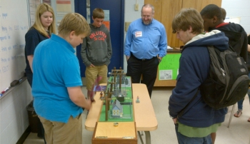 Southeastern employee, Dale Jett, uses a power system mockup to explain how power is distributed to homes.