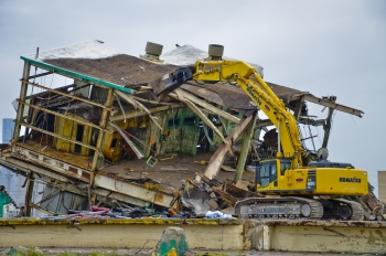 "An excavator with a shear attachment performs ""top-down"" shearing during final stages of the demolition of the C-410/C-420 UF6 Feed Plant Complex in June. Demolition debris was downsized and loaded into rail cars for shipment off site. The complex was the last of 32 inactive facilities to be removed as part of the cleanup scope that existed before commercial uranium enrichment operations ended at the Paducah Gaseous Diffusion Plant and the plant facilities were returned to DOE. (Photo by Dylan Nichols)"