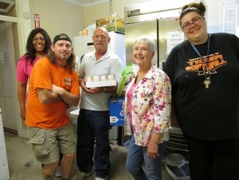 DOE's Dewintus Powell (far left) visits with (left to right) Jason Carter, Ray Osborne, Judy Dixon, and Autumn May from Pike County Outreach, a food pantry located in Waverly, Ohio, as donated food was delivered recently from the Portsmouth Site's Feds Feed Families drive.