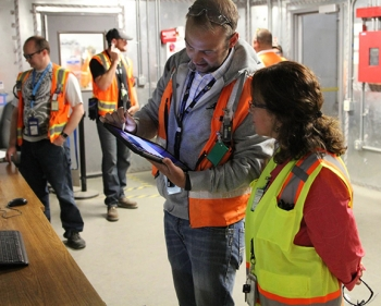 EM Assistant Secretary Monica Regalbuto, right, views the mobile device EM Idaho Site Facility Representative Nicholas Balsmeier, center, has been testing since February. With this tool, Balsmeier can easily access procedures and DOE orders and record notes that can be sent directly to EM and contractor personnel.