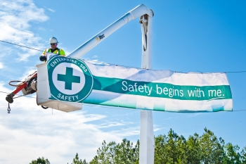 """A Savannah River Nuclear Solutions employee hangs one of several """"Safety Begins with Me"""" banners near a Savannah River Site entrance."""