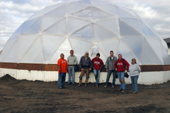 Tribal construction workers stand in front of the hexagonal greenhouse dome structure that will house the seeds for revegetation efforts.