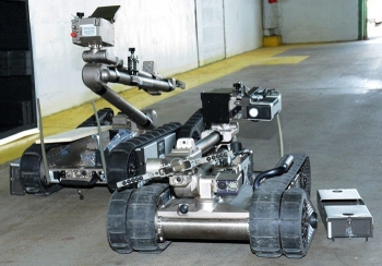 Two PackBots designed and built by Endeavor Robotics with mounted radiation sensor/communication are prepared for the demonstration.