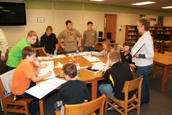 Kelly Layne of the LATA Kentucky team tells Heath Middle School students how to use zinc pennies in an experiment with differing known and unknown solutions. Facing, from left, are students Atherton Milford, McKenzie Moss, Trevor Kendall, Max Kolb, and James Michael Dodd.