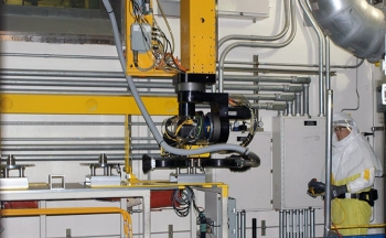 A maintenance technician works with the new box-opening gantry robot system.