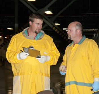 Technicians discuss equipment scans in the X-326 Process Building.