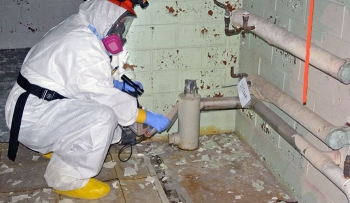 A technician surveys a pipe for contamination.