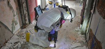 A worker takes a sample from a concrete floor.