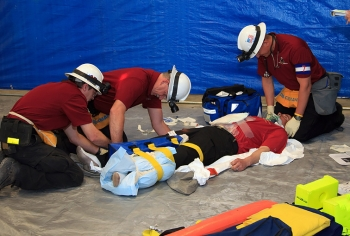 WIPP mine rescue team members simulate the proper first aid response to stabilize injuries.