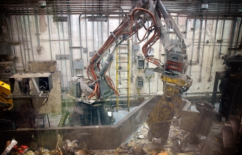 A robotic arm sorts contaminated materials in an AMWTP boxline.