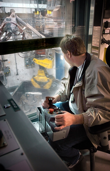 An AMWTP operator manipulates a robotic arm while sorting waste in an AMWTP boxline.