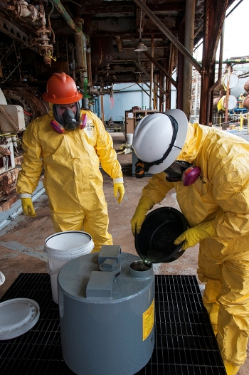 Workers pour mercury from COLEX equipment into a container designed to hold 1,000 pounds of the element.