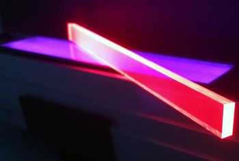 UV light shines through a sample of transparent material containing quantum dots, tiny nanoparticles that can be used to harness solar energy for electricity. | Photo courtesy of LANL.