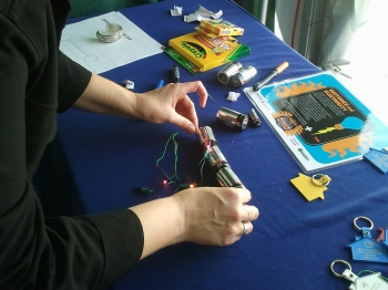 Volunteer Alison Mize demonstrates how to build an electrical circuit using a string of lights and battery at the Vehicle Technologies Program booth at the 2011 Solar Decathlon. | DOE photo, courtesy of April Saylor