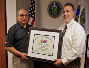 U.S. Department of Energy Carlsbad Field Office Manager Joe Franco (right) presents the Star of Excellence Award to Security Walls, LLC Manager Richard De Los Santos.
