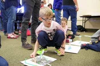 A determined young participant in the Museum of Idaho – Fluor Idaho Engineering Day puts his newly designed catapult to the test.