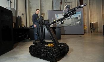 A technician at Idaho National Laboratory demonstrates the modified TALON robot.