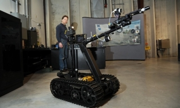 A technician at Idaho National Laboratory demonstrates the modified TALON robot.