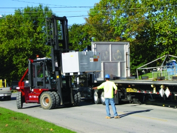 Workers load boxes containing contaminated soil that surrounded Tank W-1A.