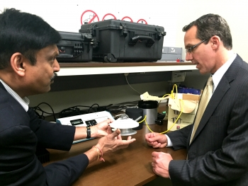Bipin Shah shows Rob Sandoli, Director of EERE International, how the cool surface testing equipment, purchased with assistance from EERE, measures energy efficiency. | Photo courtesy of EERE International