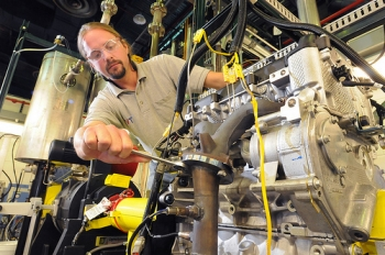 """Argonne mechanical engineer Thomas Wallner adjusts Argonne's """"omnivorous engine,"""" an automobileengine that Wallner and his colleagues have tailored to efficiently run on blends of gasoline, ethanol andbutanol.   Courtesy of: Argonne National Laboratory."""